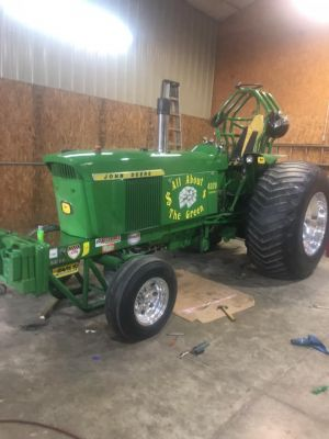 green pulling tractor parked inside a garage