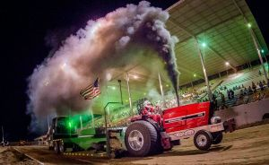 red tractor blowing smoke at tractor pulling event