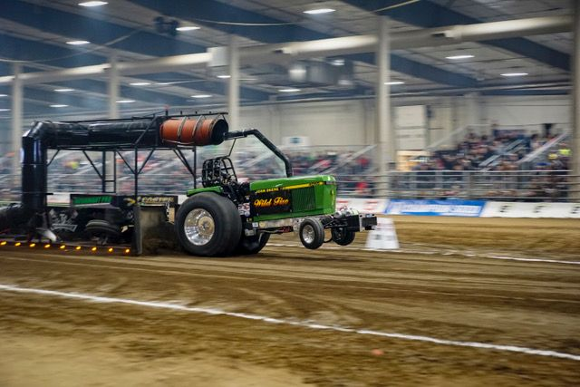indoor tractor pulling event featuring a green tractor