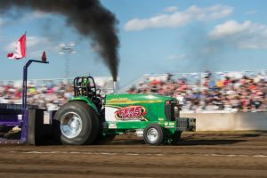 Green tractor tractor pulling with black smoke coming out the top