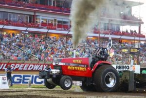 red tractor pulling in front of a crowd of people