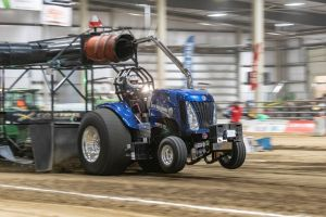 blue tractor at an indoor tractor pulling event