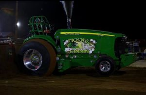 green pulling tractor outside in the evening