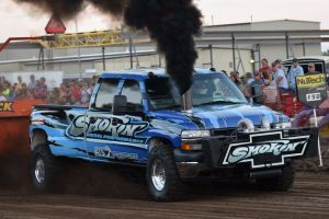 pulling truck blowing black smoke at truck pulling event