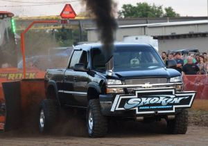 black pulling truck blowing black smoke at truck pulling event