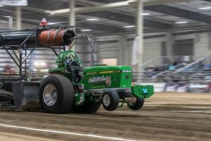green tractor pulling inside